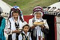 Kyrgyz women and child offering bread and salt.jpg