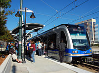 A blue and gray train stopped at a covered, side platformed station with several passengers entering.