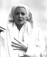 Woman in white wearing a towel on her head, clutching her chest