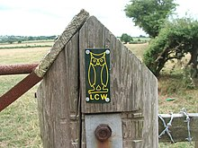 "A close-up view of a large wooden post with a pointed top. Affixed to this is a panel containing a yellow outline of an owl and the letters ""LCW"". Attached to the post are two rusty metal rails to the left and part of a wooden fence with barbed-wire to the right. In the background are several fields, with a low hill far left. To the right is a nearby tree and there is a larger one some distance behind it."