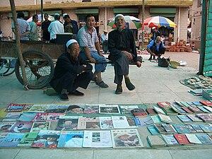 Linxia Hui Autonomous Prefecture - Two Hui book vendors at a Linxia City market, wearing traditional eyeglasses