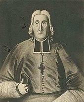 Siyah beyaz bir adam, ayin kıyafetleri giyen ve göğüs haçı öne doğru bakan, sağ elinde bir kitap ve sağ yüzük parmağında dini bir yüzük bulunan bir adamın resmi.