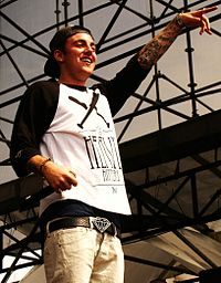 A tattooed Caucasian man holding a microphone smiles and points forward.