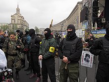 A line of five Patriot of Ukraine members (some with bats) providing security at a meeting organized by Right Sector activists, at the Euromaidan's main stage