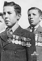 Black and white photograph of three boys. The two boys in the centre and right-hand side of the photo are wearing formal suits with medals pinned on the left-hand side of their chest. Only part of the head of the third boy is visible on the left-hand side of the photo.