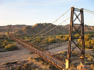 Gila River - The McPhaul Suspension Bridge on a former section of US Route 95 spans the Gila between the Gila and Laguna ranges in Yuma County. The bridge is listed on the National Register of Historic Places.