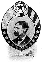 Profile of a white man with slicked down hair and a bushy mustache wearing a dark suit and bow tie. The portrait is surrounded by a circular frame with stars and stripes.