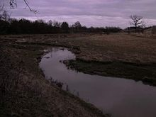 Narrow stream meandering across a flat field in winter time.