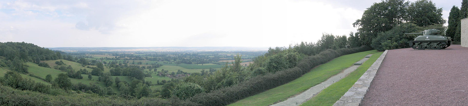 In the foreground tree-covered hills rising to the left and right frame a view over a valley. A tank and the edge of a building are on the rightmost hill. A flat plain of fields, trees and hedgerows fills the background, with a small hamlet visible in the middle-distance.