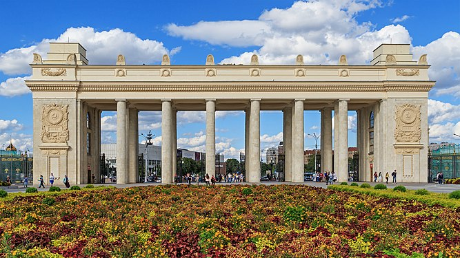Photograph of the colossal colonnade at Gorky Park's main portal in 2016, a large flowerbed in the forefront