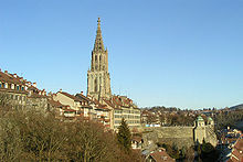 A grey stone Gothic spire rises above the Old City of Bern