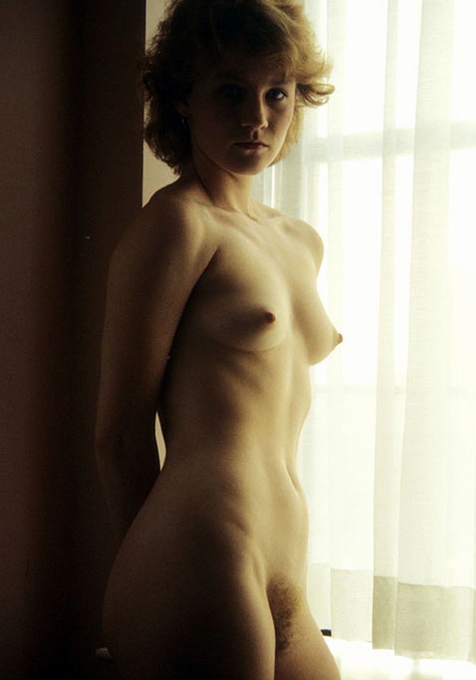 Nude blonde woman standing on window