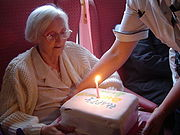 Seated elderly woman in glasses and sweater, viewing a birthday cake being placed in front of her by a nurse. The square cake has a single lit candle.