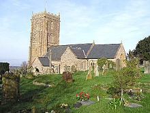 Stone building with square tower. In the foreground are gravestones.