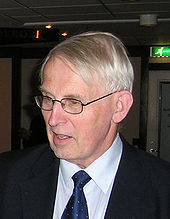 Half-portrait of a man in his seventies looking away from the viewer. He wears a suit and glasses.
