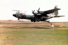 A Royal Air ForceC-130 Hercules  military plane. Its propellers attach to its wings, and it appears to be hovering just above a barren field. From the back of the aircraft, a package is being dropped onto the field from an open rear gangway.