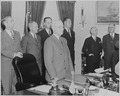 Photograph of President Truman standing at his desk in the Oval Office, with members of his Cabinet standing nearby... - NARA - 199517.tif