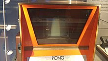 A horizontal photograph showing the top half of an orange arcade cabinet.