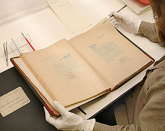 Collections care - A conservator carefully handles a book. Preventive conservation protocols protect the lifespan of cultural objects while allowing them to be viewed safely.