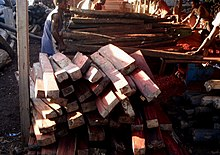 A stack of rosewood blanks sits in the foreground while a team of workers prepares additional timber in the background
