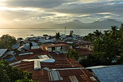 Aerial view of a Puerto Princesa barangay showing random houses and nearby bay during a sunrise