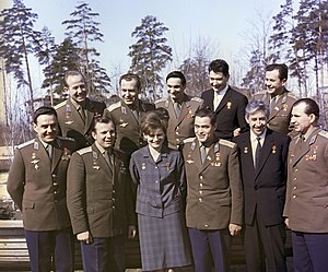 Ten men and one woman standing in two rows, five men behind and higher up than the six at the front. The woman is close to the centre of the front row. Eight of the men are in military uniform consisting of a dark khaki four-button jacket and dark blue trousers; the other three people wear civilian suits. All eleven are wearing the insignia of two awards, one on each breast; those in military uniform wear various additional insignia.