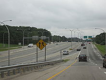 View of a three-lane collector/distributor road of a freeway; several green signs are visible in the distance. At the center of the image is a four-lane divided freeway that is separated from the distributor road by concrete barriers.