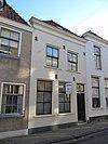 foto van Pand met verdieping en schilddak. Gepleisterde gevel met houten kroonlijst, vensters met schuiframen en deur uit de 19e eeuw