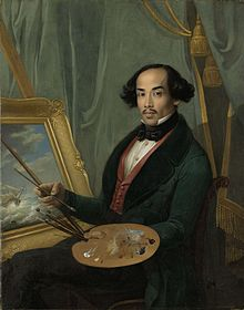 A Javanese man in a suit, holding a paintbrush