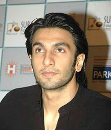 A young Indian man with sharp features looking a little up from the camera level. He wears a black t-shirt.