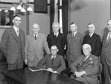 Members of Reid's cabinet gathered around a table in an office.