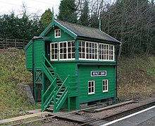 Green trackside building with stairs