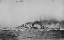 A light gray warship steaming at high speed; thick black smoke pours out of the two funnels.
