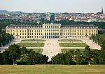 Rococo three and four story palace stretches across most of the midground. In the foreground are manacured lawns and walkways, while the background is the old city of Vienna with a cathedral on the horizon.
