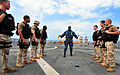 Senior Chief Petty Officer Robert Goode, a master-at-arms, center, gives pre-fire instructions to a visit, board, search and seizure team prior to a weapons shoot aboard amphibious dock landing ship USS Pearl 101018-N-KB563-243.jpg