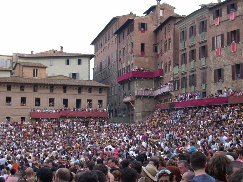 Thousands of spectators, coming from all the world, fill the Piazza del Campo to capacity on the day of the Palio di Siena. (http://upload.wikimedia.org/wikipedia/commons/thumb/b/b9/Siena_Piazza_del_Campo_20030815-375.jpg/800px-Siena_Piazza_del_Campo_20030815-375.jpg)