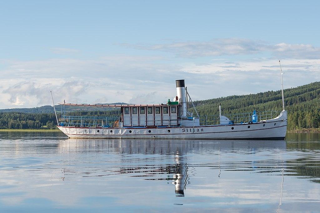 Vitt fartyg framför en grön skog och under blå himmel.