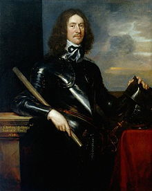 A portrait of a man dressed in black armour.  He has long brown hair down to his shoulders and a thin moustache and beard.  His left hand his holding a helmet which is resting on a pedestal.  His right hand his holding a small pole or scroll