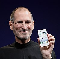 Shoulder-high portrait of smiling man in his fifties wearing a black turtle neck shirt with a day-old beard holding a phone facing the viewer in his left hand