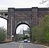 A brick arch over a road, with the start of an iron arch on the left.