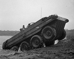 A large, open-topped, eight-wheeled vehicle emerges from a body of water and is climbing up the bank and onto land; two men are on board it.