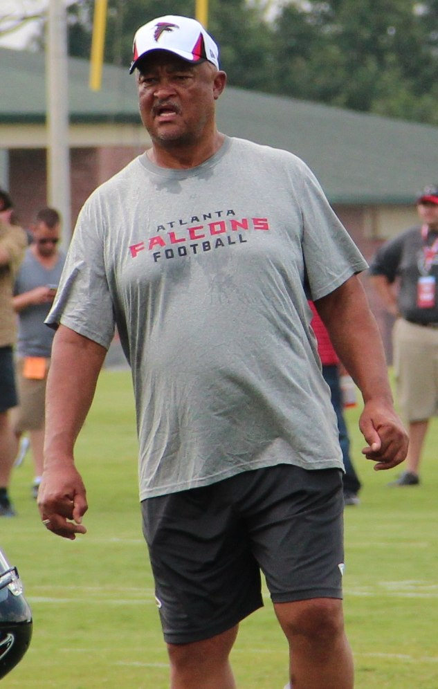 Candid knees-up photography of Robiskie on a football practice field wearing a grey Atlanta Falcon t-shirt, dark grey shorts and a white Falcons baseball cap