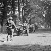 Men on foot and jeeps towing guns on a tree lined road