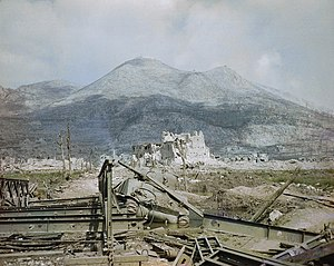 The ruins of Cassino, May 1944- a wrecked Sherman tank and Bailey bridge in the foreground, with Monastery Ridge and Castle Hill in the background. TR1799.jpg
