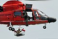U.S. Air Force Staff Sgt. James Stewart, a public affairs broadcaster with the 621st Contingency Response Wing, holds onto a rescue basket under a Coast Guard H-65 Dolphin helicopter during water survival 110818-F-CA540-714.jpg