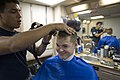 U.S. Navy Ship's Serviceman Seaman Richard Berrios, left, cuts the hair of Hull Maintenance Technician 3rd Class Ivan Knighten in the barbershop aboard the amphibious dock landing ship USS Pearl Harbor (LSD 52) 130523-N-WD757-064.jpg