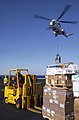 US Navy 030326-N-4308O-016 Flightdeck personnel use forklifts to position cargo as an SA-332 Super Puma helicopter is used to airlift supplies from the Military Sealift Command ship USNS Saturn (AFS 10) to the flight deck of US.jpg