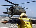 US Navy 040814-N-0000X-005 Boatswain's Mate 1st Class Tony Cloud assigned to the guided missile frigate USS Gary (FFG 51) signals a U.S. Army UH-60A Blackhawk to hover.jpg