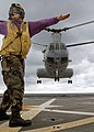 US Navy 070612-N-5067K-062 Aviation Boatswain's Mate Airman Lowel A. Shorey III, a landing signalman enlisted (LSE), signals and checks the horizon for a Marine CH-46 Sea Knight taking-off from amphibious transport dock USS Jun.jpg
