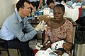 US Navy 070903-N-6020F-041 Hospital Corpsman 3rd Class Daniel Sena, attached to Military Sealift Command hospital ship USNS Comfort (T-AH 20), gives a patient an immunization shot at Centre Hospitalier Eliazar Germain in Pétion.jpg